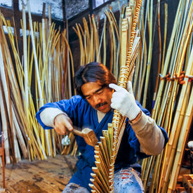 Chibata Kanjuro, whose family has been making bows since the 15th century, bends the bamboo frame of a new bow in his workshop in Kyoto