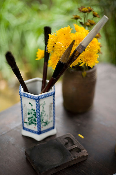 Caligraphy brushes, an ink stone and flowers