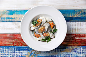 Shellfish Mussels Clams on plate with blue cheese sauce and parsley