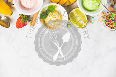 Top view of ice cream in white bowls and fresh ingredients on white marble background. Pink (strawberry), yellow (mango or banana) and green (lime, green tea or pistachio).