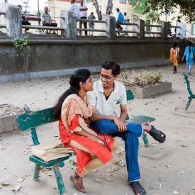 A young couple sit and talk together in the afternoon on the Strand by the Hoogley River