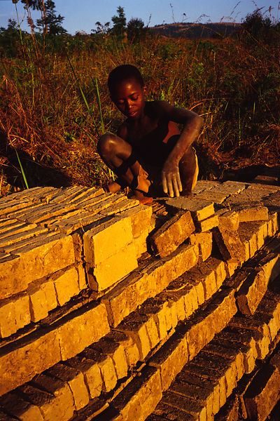 Burundi - Ruyigi - A child piles bricks in in a stack as part of his job in a brick factory