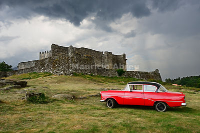 The 13th century old castle of Lindoso, keeping an eye on the Spanish mountains ahead, and a vintage Opel Rekord. Peneda Geres National Park, Portugal