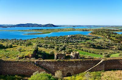 Alqueva dam, the largest artificial lake in Western Europe. In the foreground, the castle walls of Mourão. Alentejo, Portugal