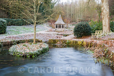 An icy pond with summerhouse beyond in a formal garden in winter.