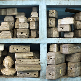 Moulds of various statues on shelves in the studio