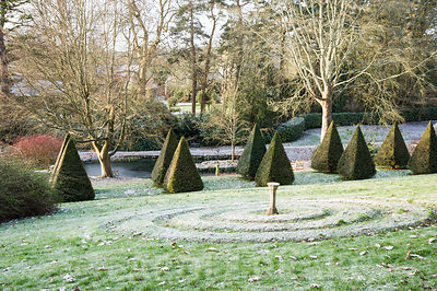 An avenue of clipped yew pyramids runs through the centre of the garden with circular feature on the slope above.