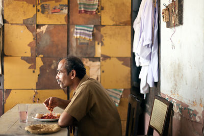 India - Alappuzha - A worker takes a quick breakfast in the staff room at the Indian Coffee House