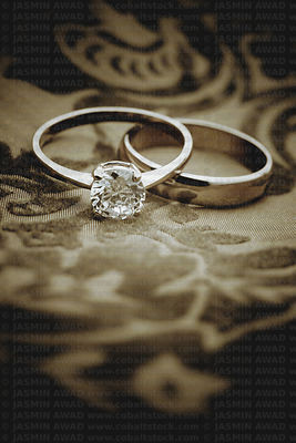 Gold wedding rings on elegant background with texture digital filtering