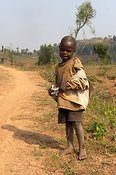 Poor child on roadside in tattered clothing. Rwanda.