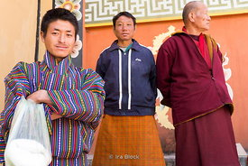 Local men in traditional costumes and a monk on the street in Paro, Bhutan.