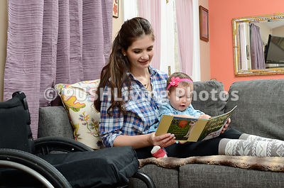 Young woman using a wheelchair reading to her baby