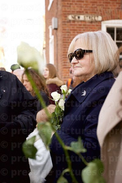 Woman in the Crowd Holding a White Rose