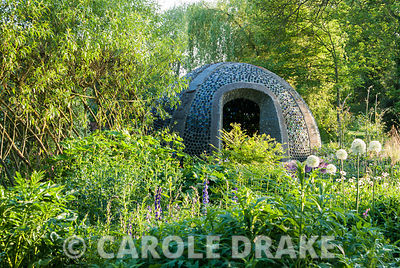 Dome structure constructed using empty bottles, with white Allium stipitatum 'Mount Everest' in foreground. Westonbury Mill Water Garden, Pembridge, Herefordshire, UK
