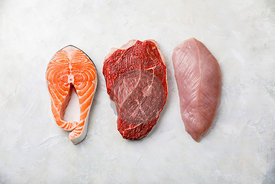 Raw food Salmon oily fish steak, beef meat and turkey breast on white textured background
