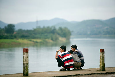 Men sitting on the banks of the Song Houng