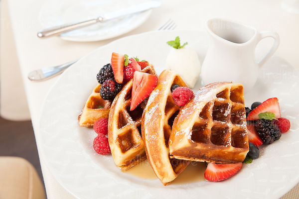 Waffles with berries on a white plate on a table for breakfast