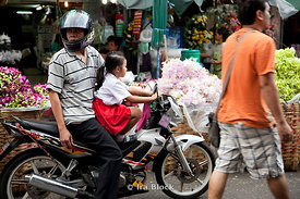 A man tries to weave his motor bike through the flower market in Bangkok, Thailand with his daughter  sitting up front.