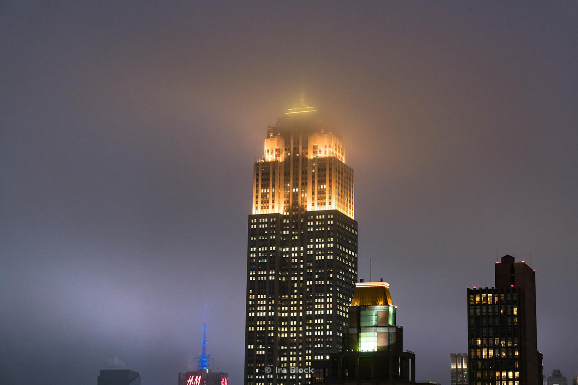 A view of the Empire State Building covered in fog in New York City.