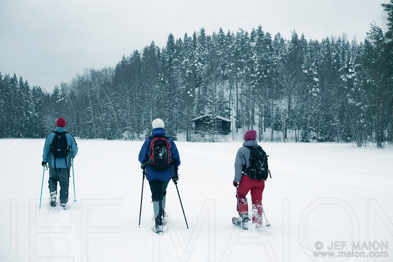 Snowshoers on frozen lake approach hut