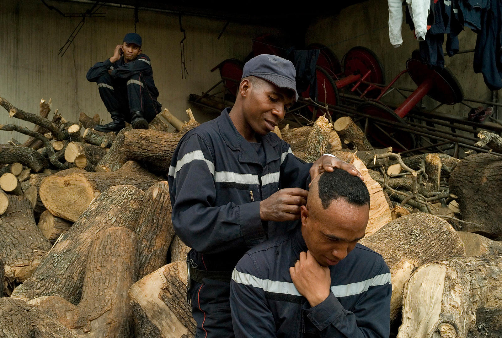 Firemen getting a haircut on a stack of wood.