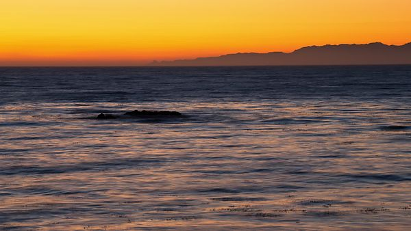Wide Shot: Dark Pacific Waters & Silhouettes Of Santa Monica's Mountains Below A Golden Ring Of Venus