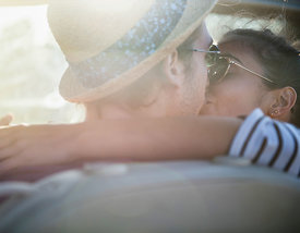 Rear view. A young couple kissing in a convertible car