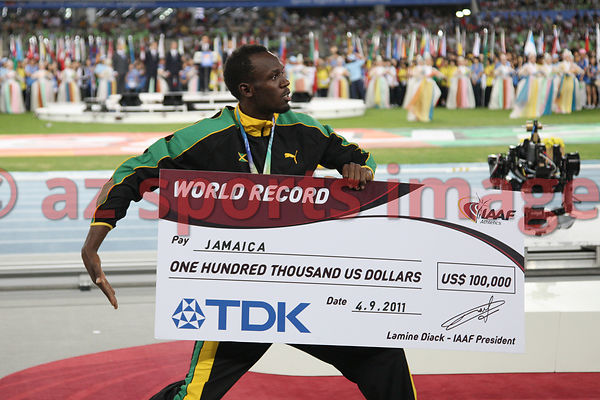 The Jamaican 4x100m team set a new world record of 37.04 at the IAAF World Championships.Usain Bolt celebrates their victory with gold medals and a check for $100,000.