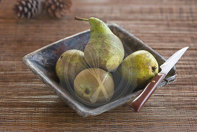 conference pears and knife .in ceramic blue dish on table with woven mat