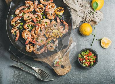 Grilled tiger prawns in cast iron grilling pan with lemon, leek, chili pepper and mint salsa sauce over grey concrete background