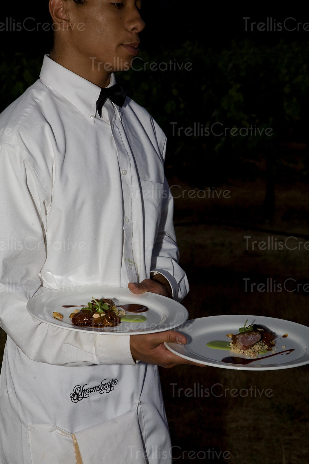 A young waiter serves the main course
