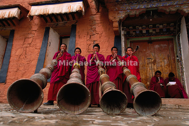 Labrang Monastery, novice monks (trapa), practice blowing the dungchen, traditional 13-foot horns, that will be used in Buddhist ceremonies and call to prayer. The sound can be compared to the singing of elephants.