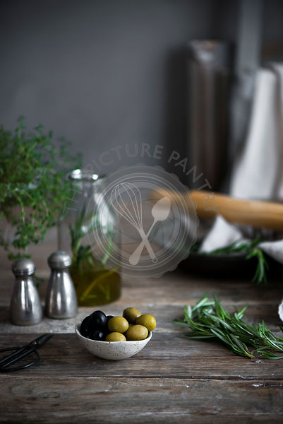 Rosemary on a vintage table with olives