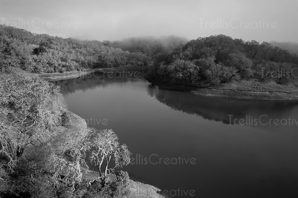 Aerial view of meandering river with the fog lifting around it.