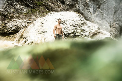 Athletic man standing in water of a brook