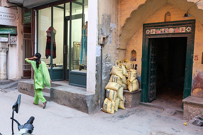 India - Delhi - A traditionally dressed woman walks past a modern upscale shop in the trendy village of Sharpur Jat now home to expensive couture and the burgeoning fashion industry