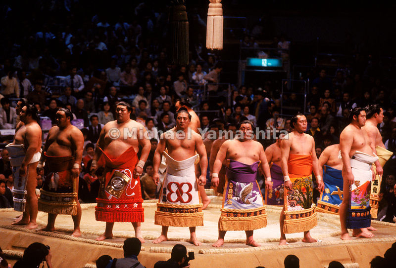 A group of sumotori lined up on the edge of the dohyo during a tournament in Osaka. Sumo is not only a time-honored ritual with arcane customs of religious significance, but also a highly-popular sport with results appearing on the front pages of sports tabloids.