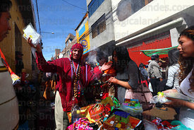 Aymara shaman blessing miniature college degree certificates at Alasitas festival, Puno, Peru