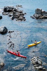 Two kayakers manouver in shallow water amongst the rocks of the Costa Brava, Spain, near the town of Calella de Palafrugell