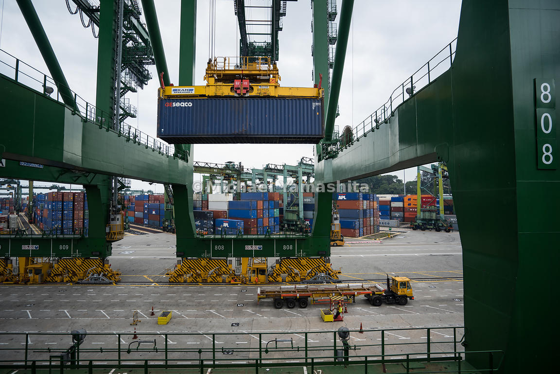 A quay crane moves containers from prime movers to a waiting ship.