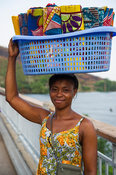 Woman carrying kikois for sale on the  suspension bridge over the Lower Volta river, Akosombo, Ghana