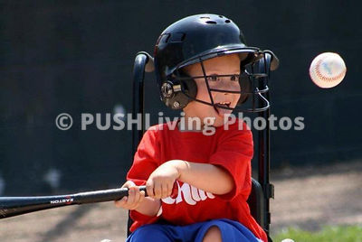 Young boy in a wheelchair playing baseball