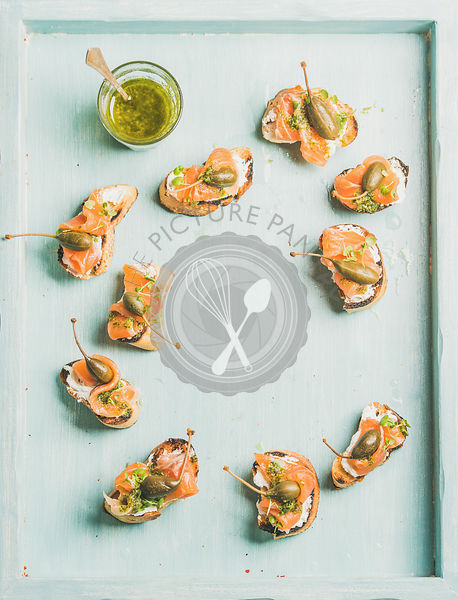 Crostini with smocked salmon, pesto sauce, watercress and capers over light blue background, top view,
