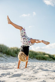 Younger Nordic boy doing a handstand on beach