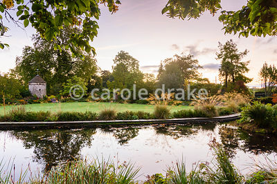 A curved pond edged with Stipa gigantea with a dovecote beyond in the Round Garden at Llanover Gardens, Monmouthshire in September