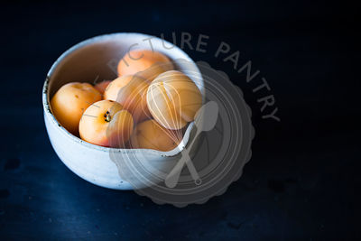 Peaches in a bowl on a dark background