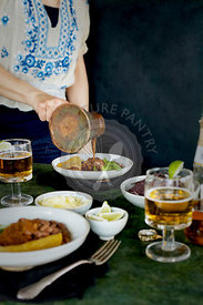Women pouring Ranchero Sauce with a vintage copper ladle.  Photographed on a green background.