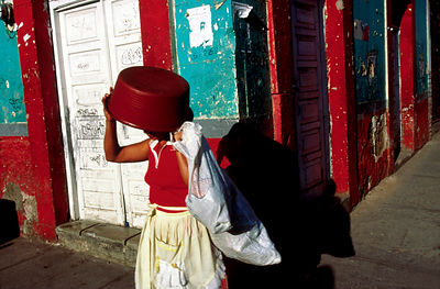 A woman uses a bowl to shield her eyes from the sun, Tegucigalpa, Honduras
