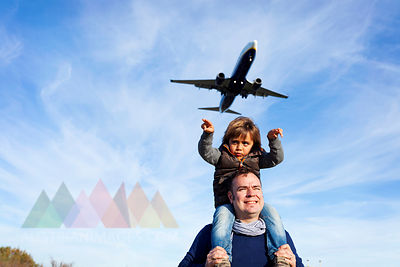 Father carrying son on shoulders under flying airplane