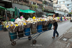 A man pushes a large cart full of wrapped up flower bouquets through the street makret in Bangkok, Thailand.